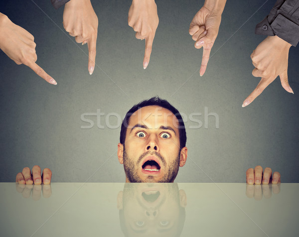 Scared man employee hiding under the table being accused by people who point fingers at him  Stock photo © ichiosea