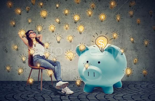 casual businesswoman with big piggy bank relaxing sitting on chair Stock photo © ichiosea
