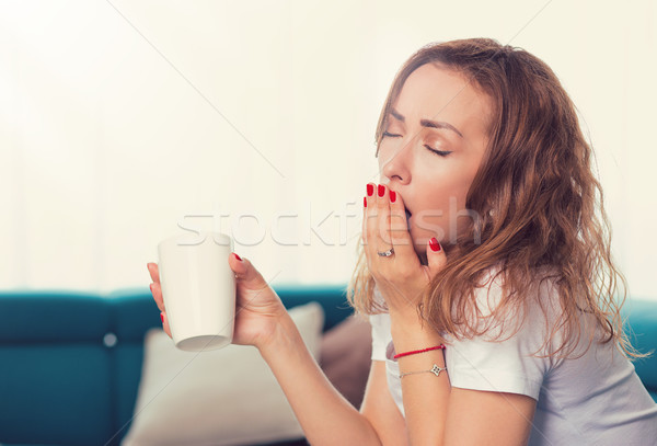 young woman sitting on sofa with cup of coffee and yawning Stock photo © ichiosea