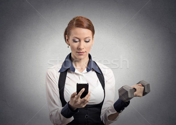 woman reading news on smartphone lifting dumbbell  Stock photo © ichiosea