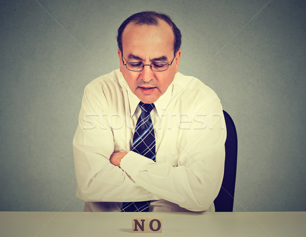 Serious worried middle aged business man sitting at table looking at word no  Stock photo © ichiosea