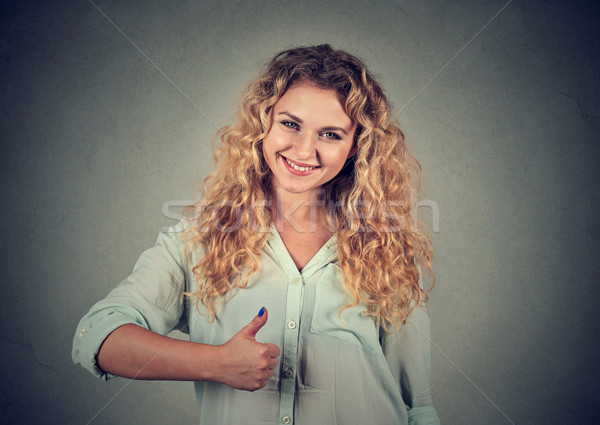 A smiling girl raises her right thumb up Stock photo © ichiosea