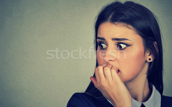 Stock photo: hesitant nervous woman biting her fingernails craving anxious