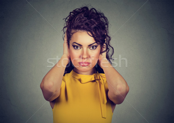 Attractive woman covering with hands her ears looking at camera  Stock photo © ichiosea