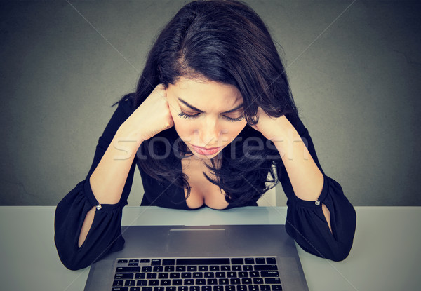 Desperate businesswoman worried after bankruptcy sitting at desk in her office in front of laptop  Stock photo © ichiosea
