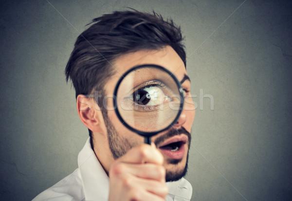 Curioso hombre mirando lupa joven cara Foto stock © ichiosea