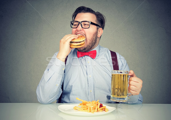 man eating junk food drinking beer Stock photo © ichiosea