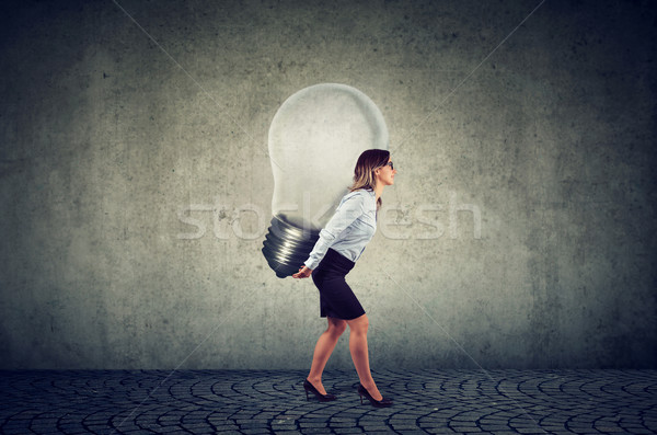 Businesswoman with business idea light bulb on her back Stock photo © ichiosea