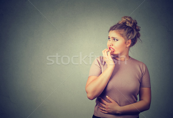 nervous stressed young concerned woman biting fingernails looking anxiously Stock photo © ichiosea