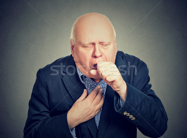 Old man coughing holding fist to mouth  Stock photo © ichiosea