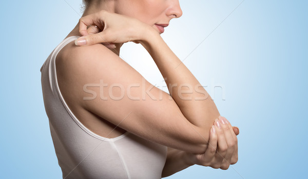 Arm pain and injury concept. Closeup side profile woman with painful elbow Stock photo © ichiosea