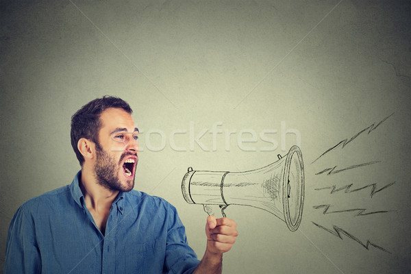 angry young man holding screaming in megaphone Stock photo © ichiosea