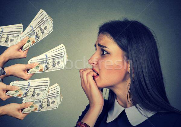 Anxious woman looking at money dollars offered by suspicious people  Stock photo © ichiosea