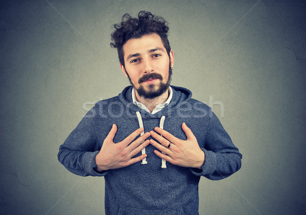 Stock photo: Faithful man keeps hands on chest near heart, shows kindness expresses sincere emotions