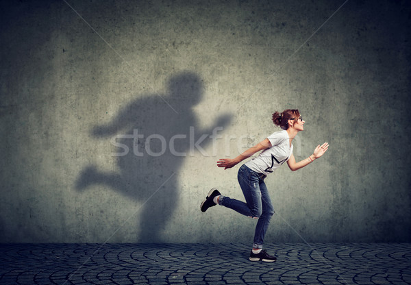 Woman running away from her fat shadow on the wall Stock photo © ichiosea