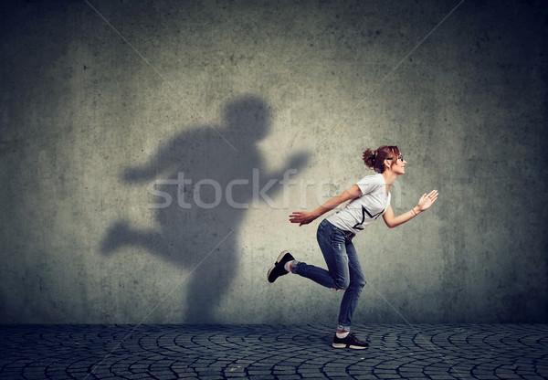 Kobieta uruchomiony z dala tłuszczu cień ściany Zdjęcia stock © ichiosea