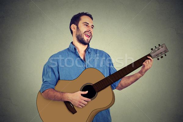 Guapo músico jugando guitarra cantando canción Foto stock © ichiosea