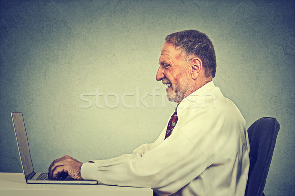 Happy smiling man typing on his laptop computer  Stock photo © ichiosea