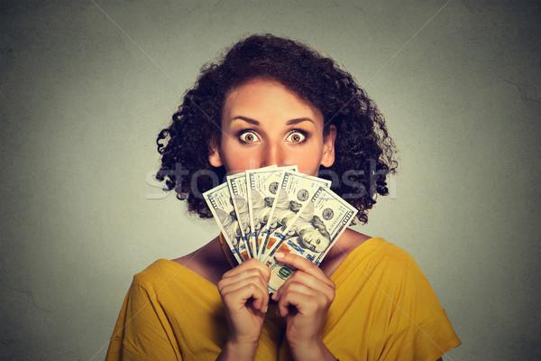 Scared looking woman hiding picking through dollar banknotes  Stock photo © ichiosea
