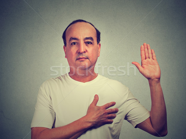 Middle aged man making a promise isolated on gray wall background Stock photo © ichiosea