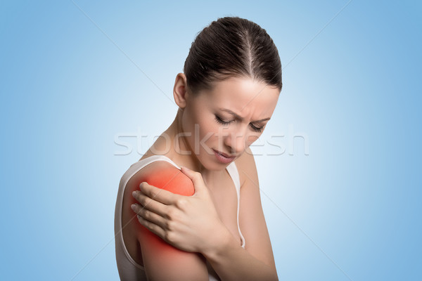 Injured joint. Young woman patient in pain having painful shoulder colored in red.  Stock photo © ichiosea