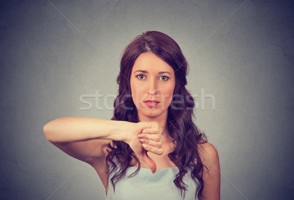 Unhappy woman giving thumbs down gesture looking with negative expression and disapproval Stock photo © ichiosea
