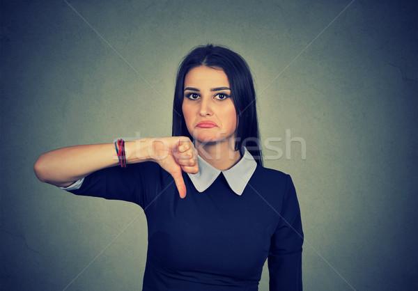 Boldogtalan nő hüvelykujj lefelé kézmozdulat néz Stock fotó © ichiosea