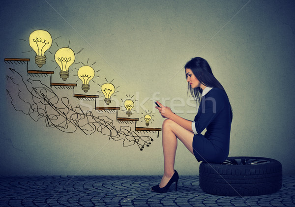 Woman sitting on wheel in front of growing up light bulbs using mobile phone  Stock photo © ichiosea
