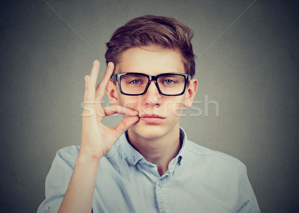 Stock photo: Keep a secret, young man zipping his mouth shut. Quiet concept