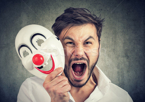 angry screaming man taking off a clown mask  Stock photo © ichiosea