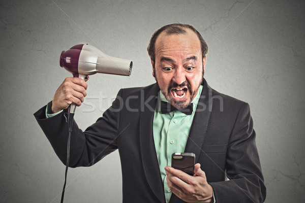 angry man screaming looking on smartphone holding hairdryer  Stock photo © ichiosea