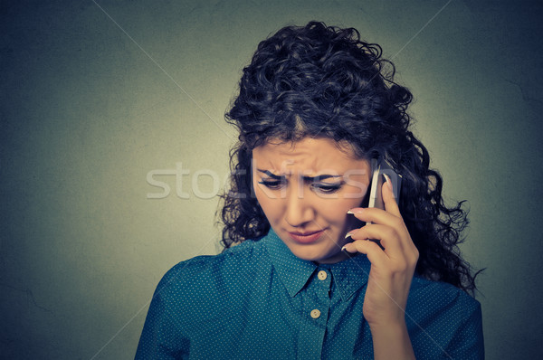 Unhappy woman talking on mobile phone looking down. Human face expression Stock photo © ichiosea