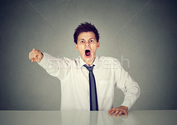 Angry young business man sitting at his desk and screaming Stock photo © ichiosea