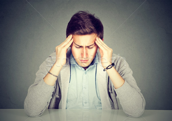 Desperate sad young man leaning on a desk Stock photo © ichiosea