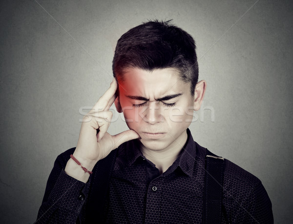 Man having a headache touching with hand temple colored in red  Stock photo © ichiosea