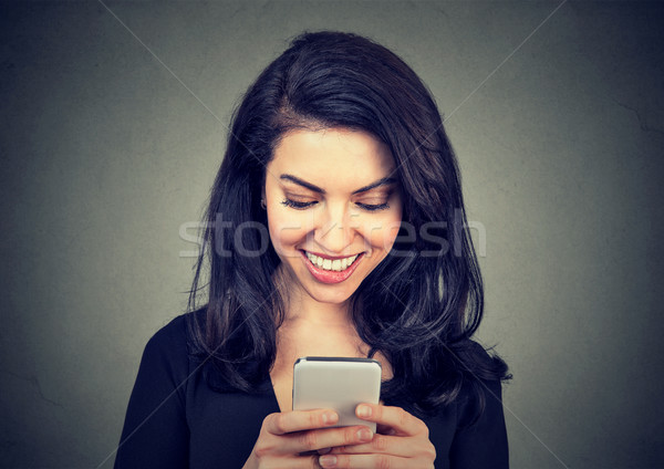Laughing woman text messaging on smart phone having a pleasant chart conversation  Stock photo © ichiosea