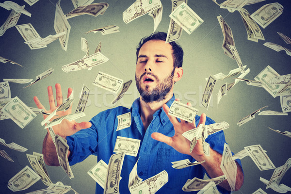 business man with eyes closed trying to catch dollar bills flying in air walking through money rain Stock photo © ichiosea