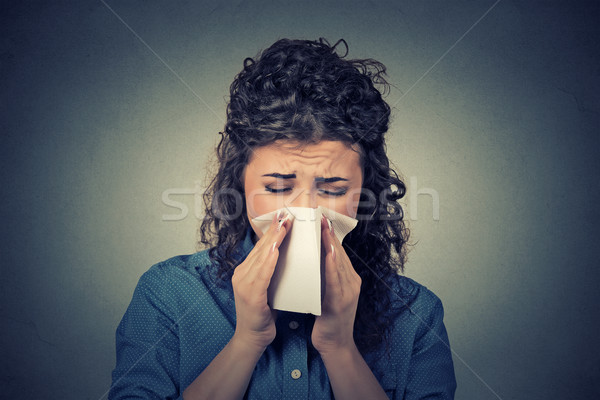 Closeup portrait woman sneezing in a tissue blowing her runny nose Stock photo © ichiosea