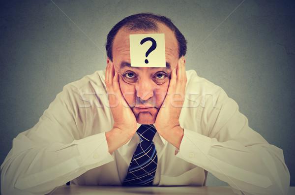 Tanácstalan üzletember kérdőjel ül asztal izolált Stock fotó © ichiosea