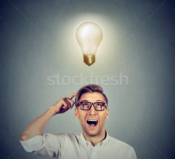 Happy man in glasses looking up at bright light idea bulb above head  Stock photo © ichiosea