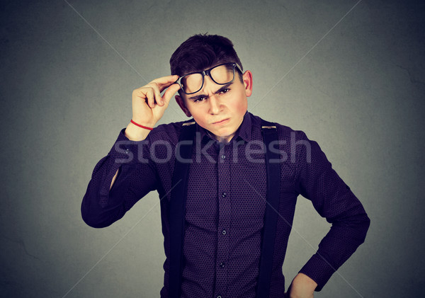 Funny looking skeptical grumpy young man in glasses   Stock photo © ichiosea