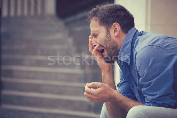 sorrowful crying man sitting on steps outdoors  Stock photo © ichiosea