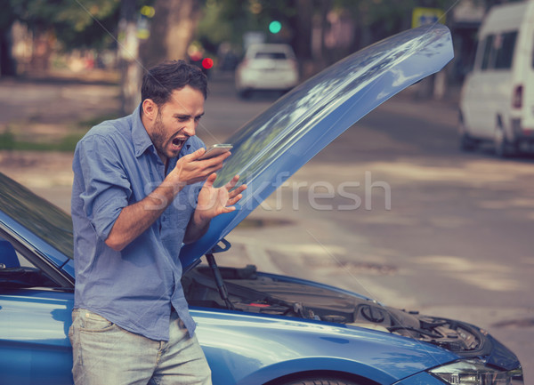 Frustrated young man calling roadside assistance after breaking down Stock photo © ichiosea