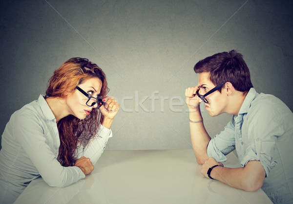 Angry man and woman sitting at table looking at each other with hatred and disgust  Stock photo © ichiosea