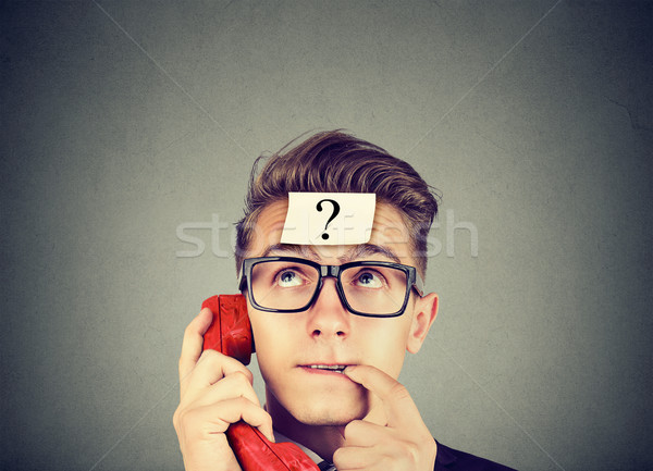 Perplexed man with question mark having a telephone conversation   Stock photo © ichiosea