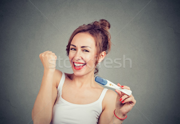 Excited woman with positive pregnancy test Stock photo © ichiosea
