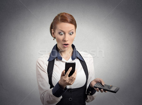 Stock photo: Shocked woman looking on smart phone holding calculator