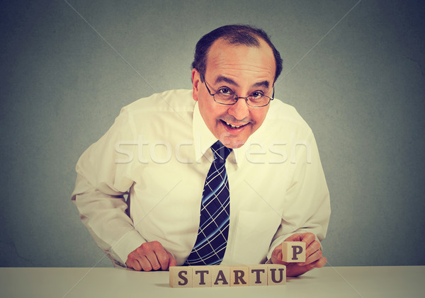 Businessman arranging wooden cubes in structure reading start up. Concept of business entrepreneursh Stock photo © ichiosea