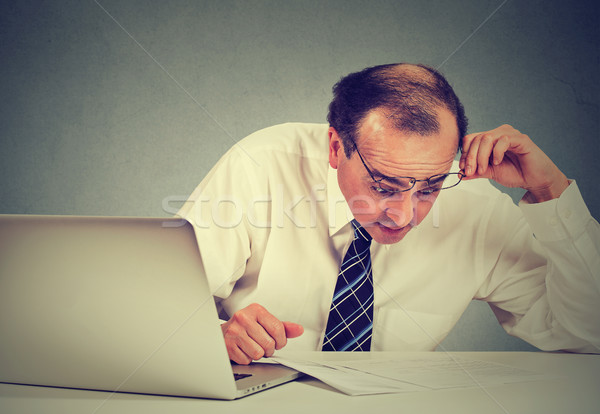Confused surprised business man looking at documents. Stock photo © ichiosea