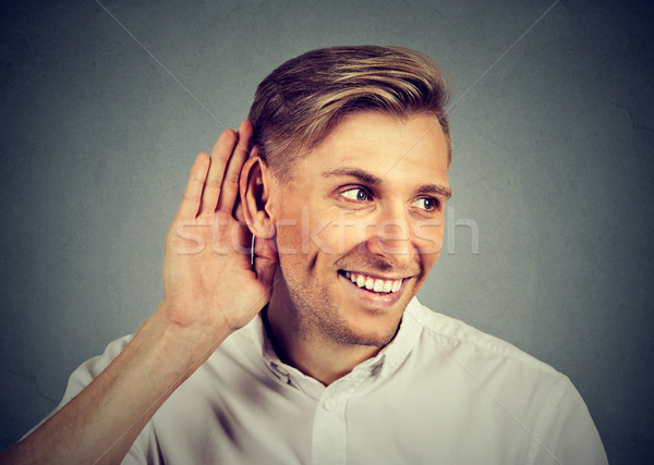 nosy man secretly listening in on conversation hand to ear Stock photo © ichiosea
